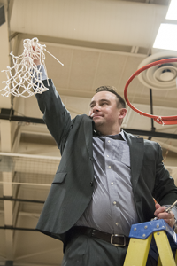 Coach Ben Conrad holds up the winning net from the Saturday, March 21 national championship victory. The game marked Conrad's 300th career win. Photo by Julia Larberg