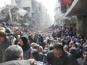 Residents wait to receive food aid distributed by the U.N. Relief and Works Agency at the besieged al-Yarmouk camp, south of Damascus on Jan. 31, 2014. Photo courtesy of REUTERS/UNRWA/HANDOUT via Reuters