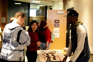 Members of the Student Senate hangout at a table encouraging people to vote.  Three display boards show the profiles of each candidate in their respective position of interest. Photo by Andrew Hartnett