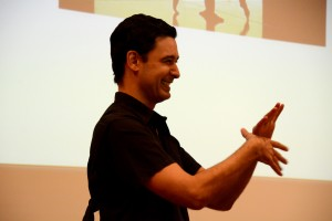 Bokaer laughs as he teaches a hand exercise to the audience. He takes both hands and moves the webs of them together in order to help circulation. Photo by Andrew Hartnett.