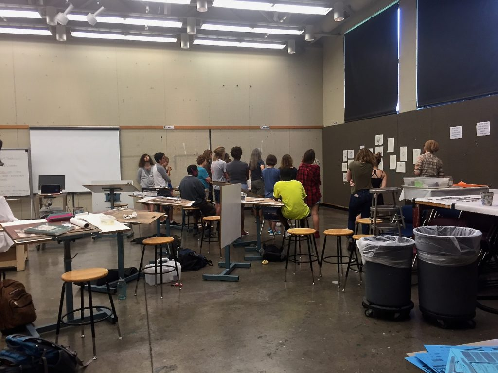 Painting students engaged in critical discussions prior to an assignment