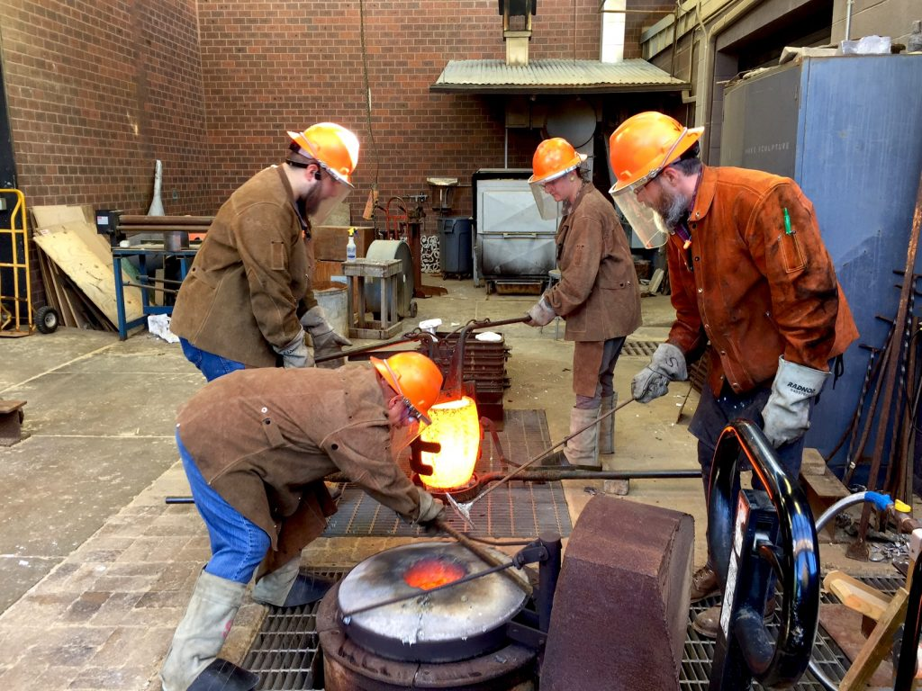 The Crucible of liquid bronze is lifted from the furnace.